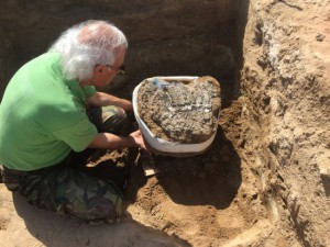Karol Pieta vyzdvihuje in situ blok s pozostatkami košíka upleteného z palmových listov.